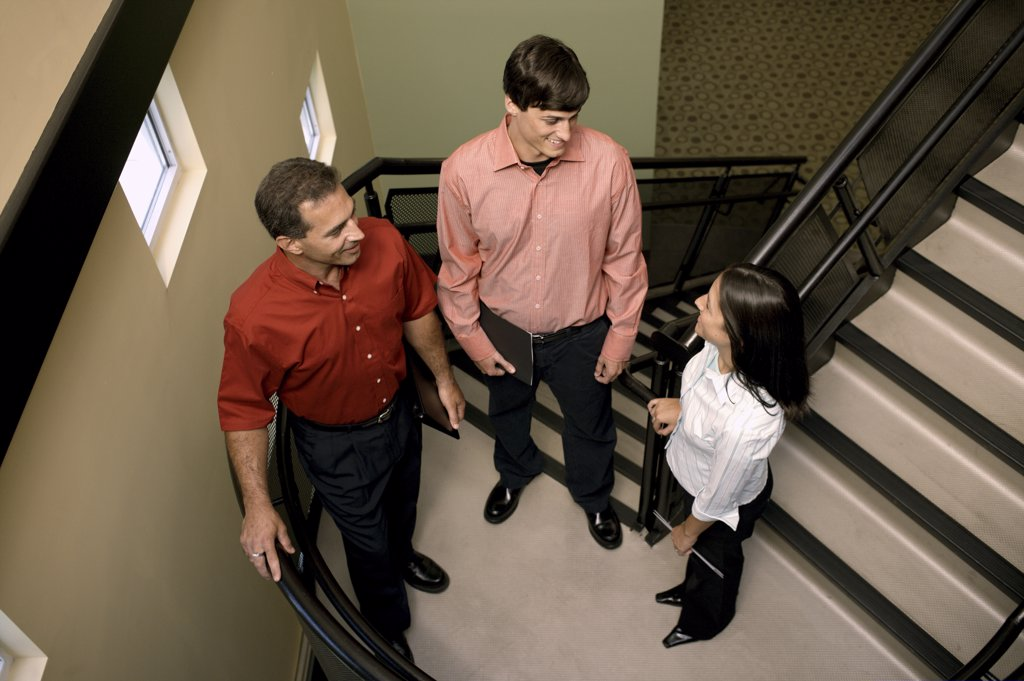 High angle view of two businessmen and a businesswoman standing on stairs : Stock Photo