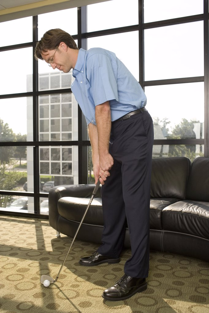 Businessman playing golf in an office : Stock Photo
