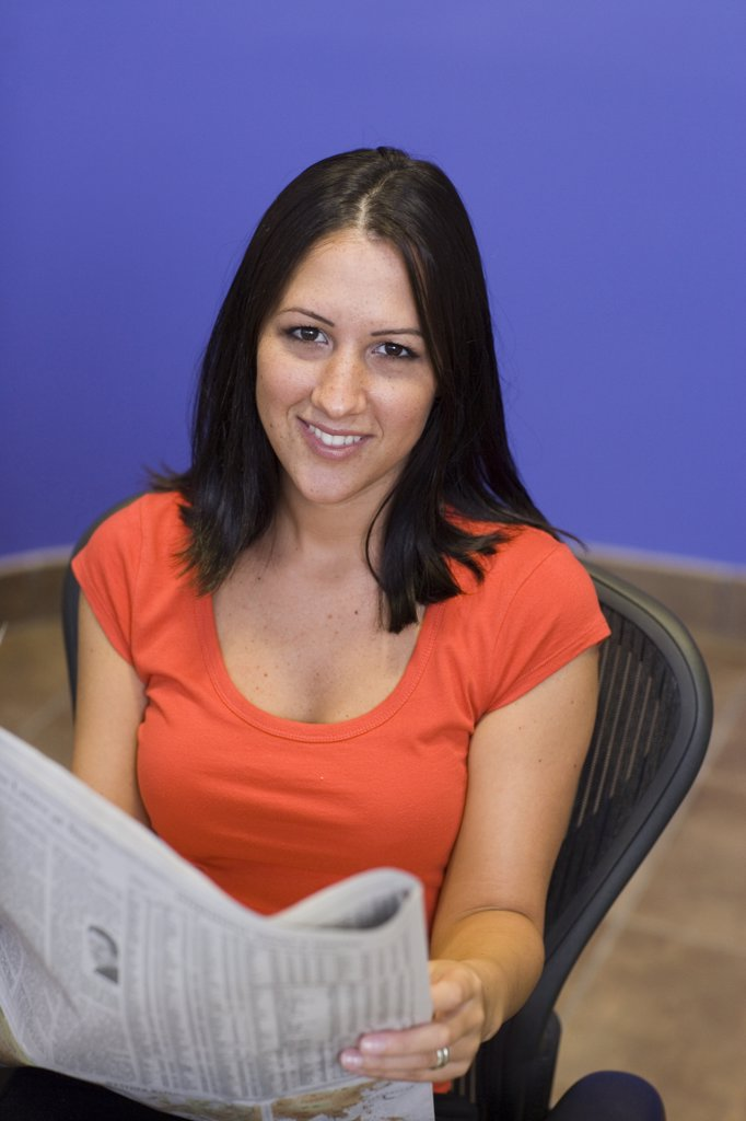 Portrait of a businesswoman holding a newspaper in an office : Stock Photo