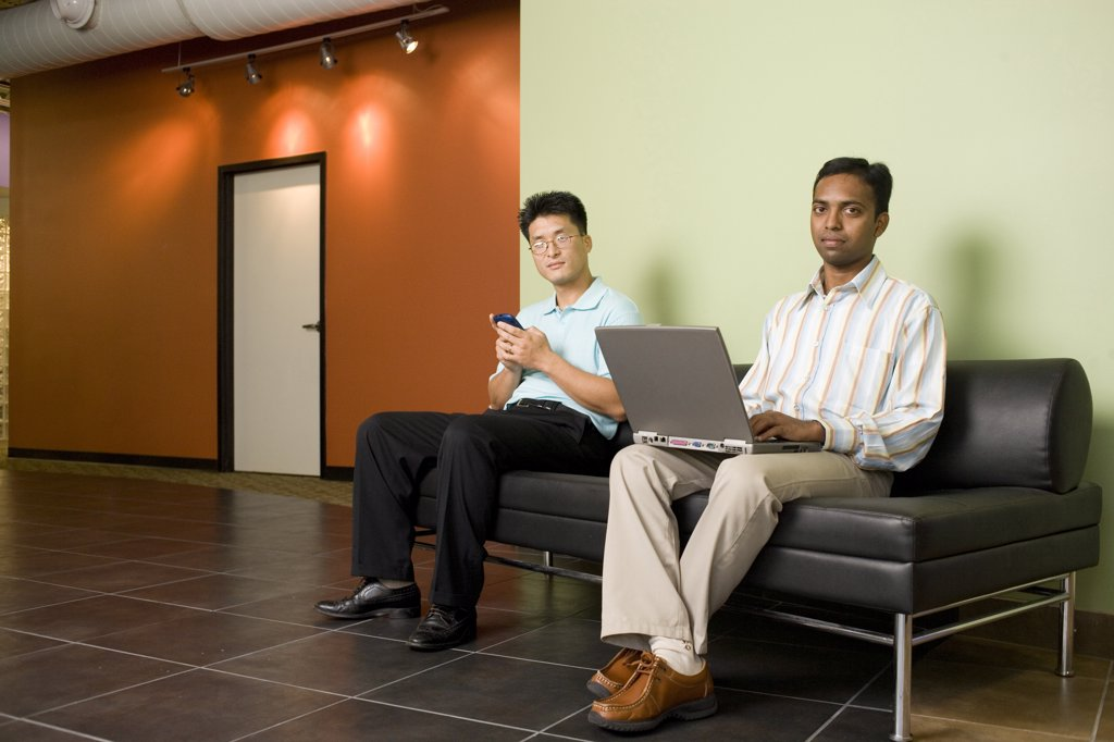 Portrait of two businessmen sitting on a couch in an office : Stock Photo