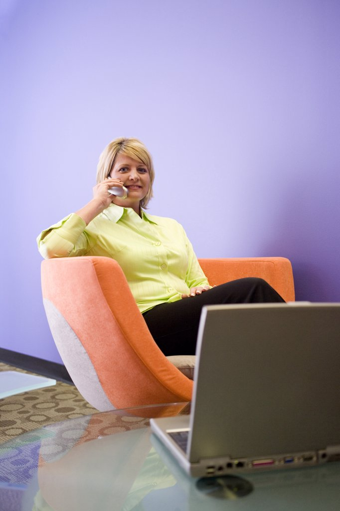 Portrait of a businesswoman talking on a mobile phone in an office : Stock Photo