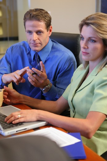 Businessman sitting with a businesswoman : Stock Photo