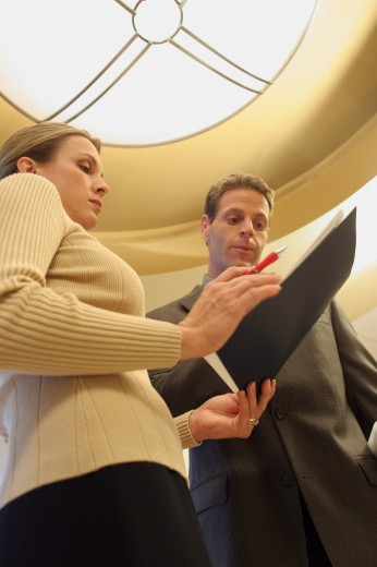 Stock Photo: 1574R-06709 Low angle view of a businessman talking to a businesswoman