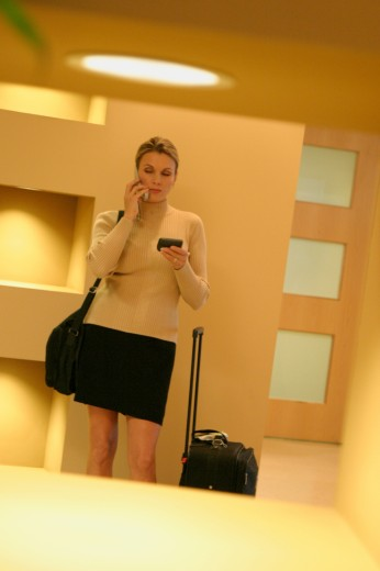 Stock Photo: 1574R-06793 Businesswoman standing in a corridor using a mobile phone