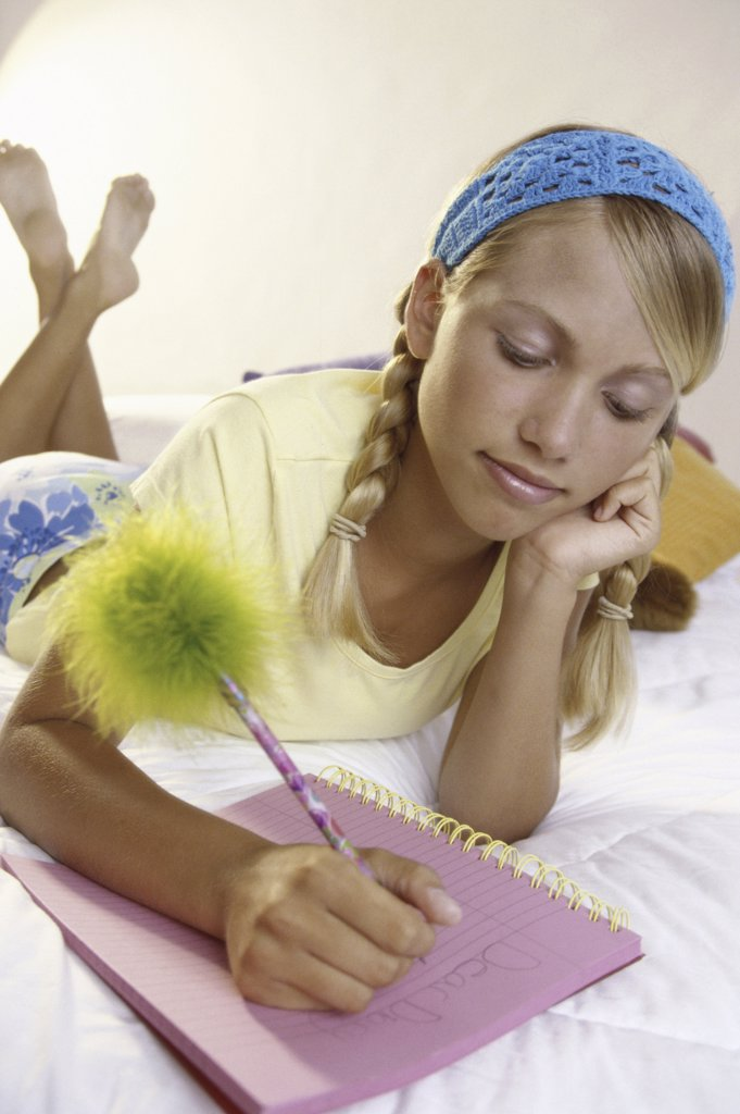 Teenage girl writing in a notebook : Stock Photo