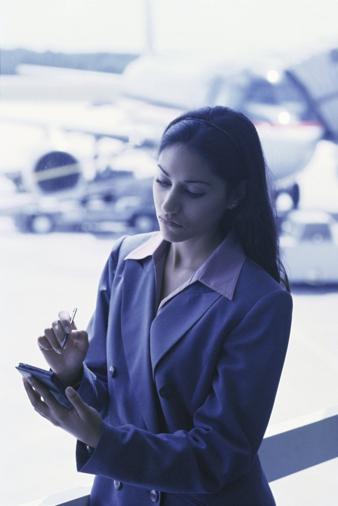 Businesswoman operating a hand held device : Stock Photo