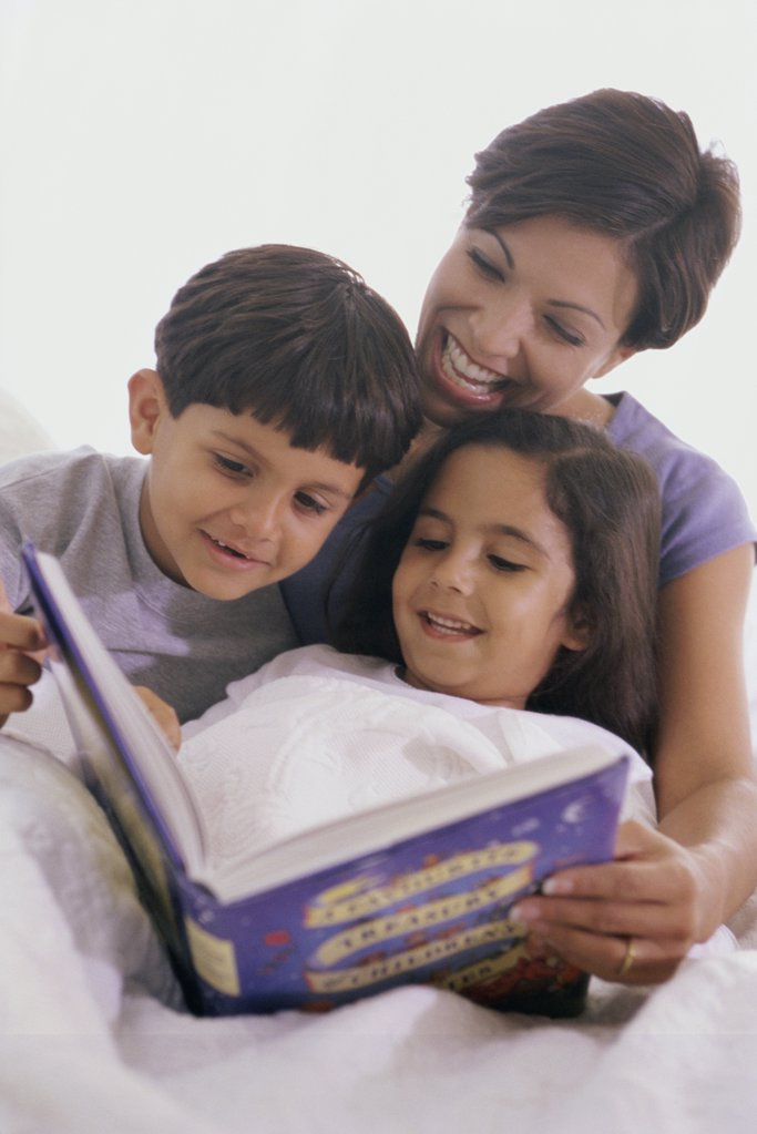 Stock Photo: 1574R-0689B Mother and her two children reading a book