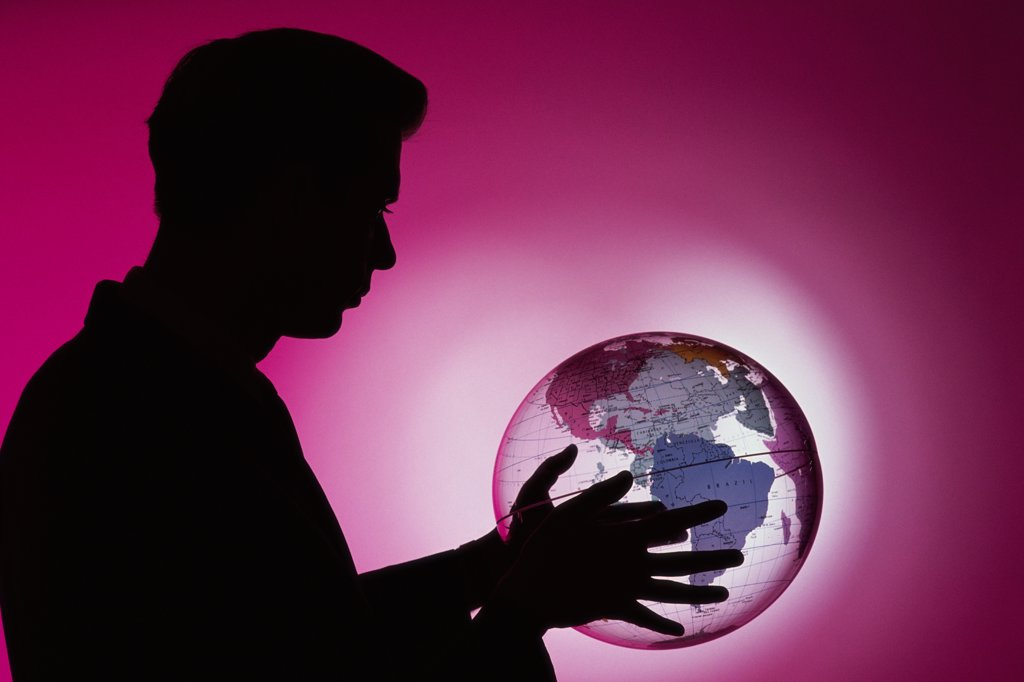 Side profile of a businessman holding a globe : Stock Photo
