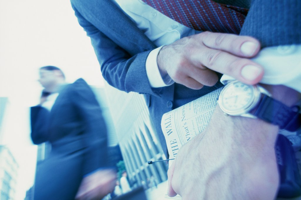 Businessman looking at his wristwatch : Stock Photo
