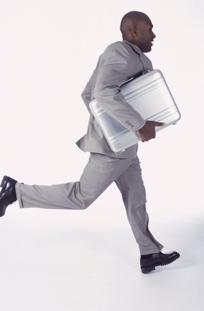 Stock Photo: 1574R-07103 Side profile of a businessman running with a briefcase