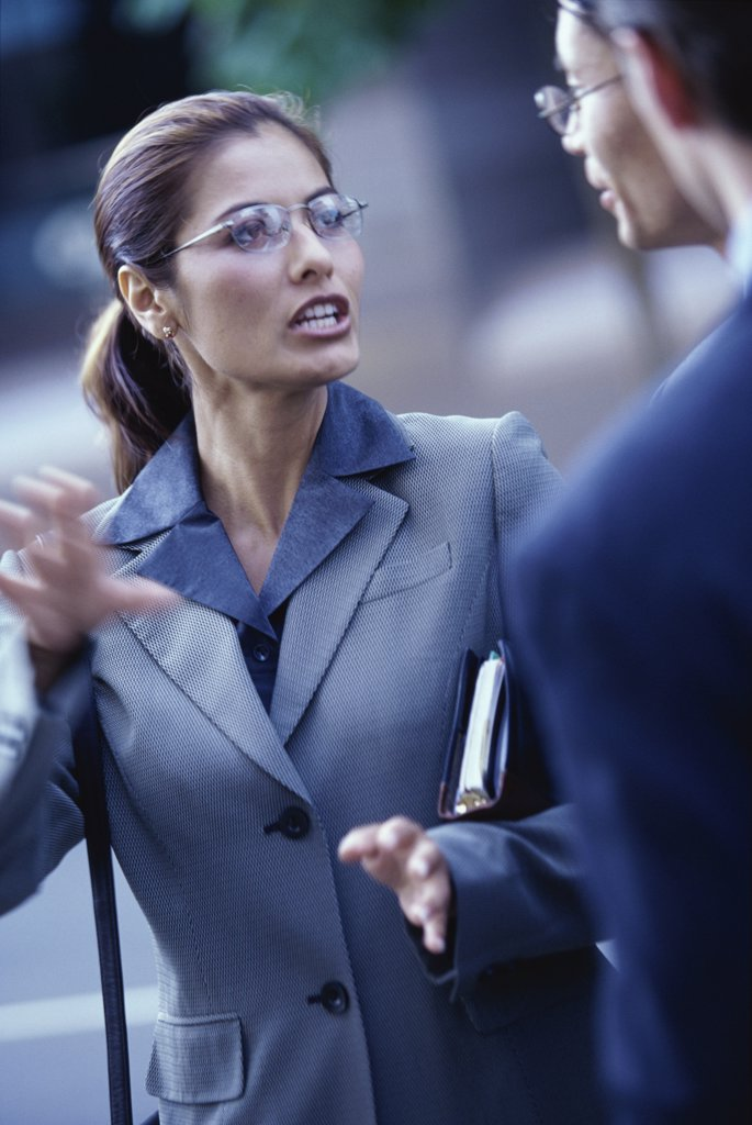 Close-up of two businessmen and a businesswoman talking : Stock Photo