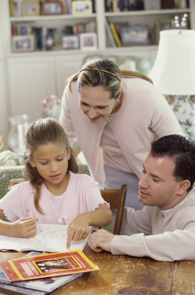 Parents helping their daughter study : Stock Photo