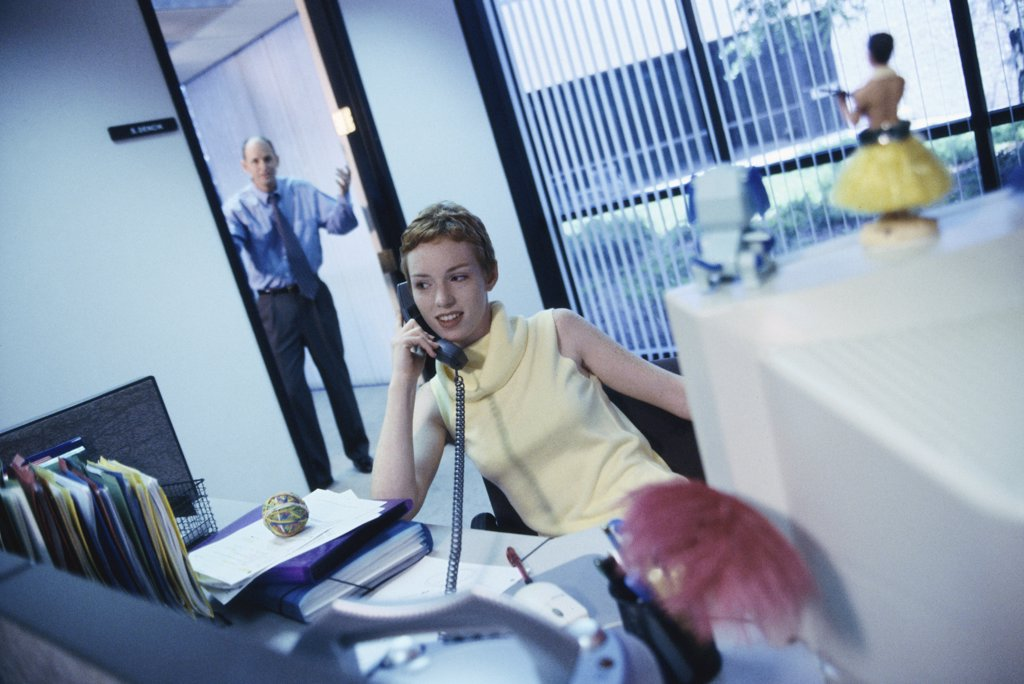 Secretary talking on a telephone with a businessman standing in a doorway behind : Stock Photo