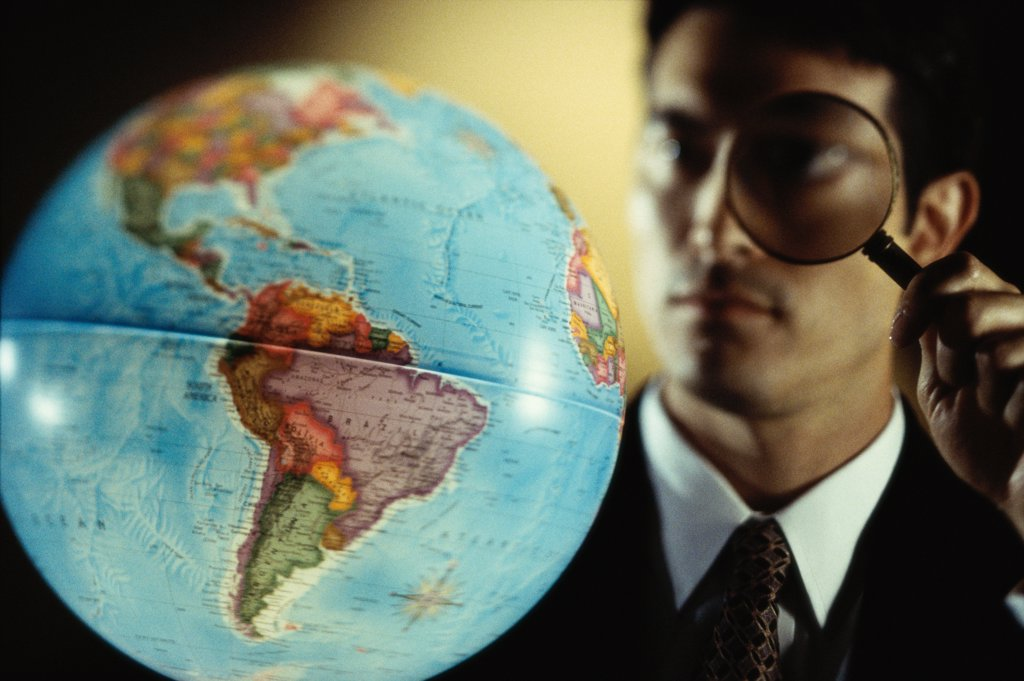 Stock Photo: 1574R-0751A Close-up of a businessman looking through a magnifying glass at a globe