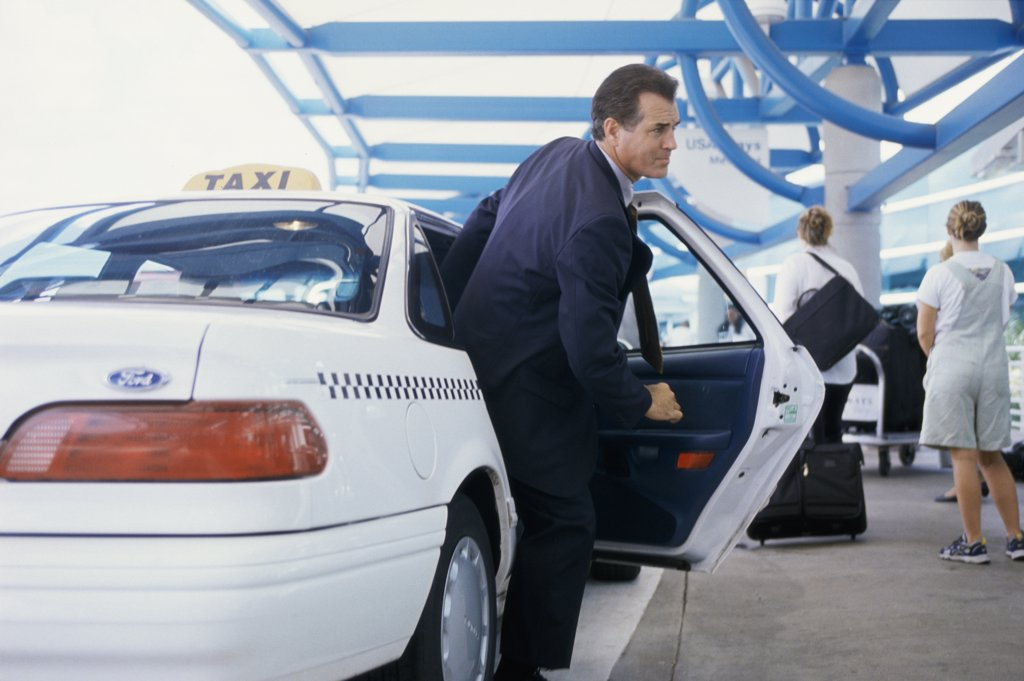Businessman getting out of a taxi outside an airport : Stock Photo
