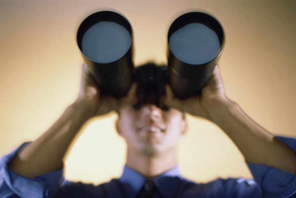 Businessman looking through a pair of binoculars : Stock Photo
