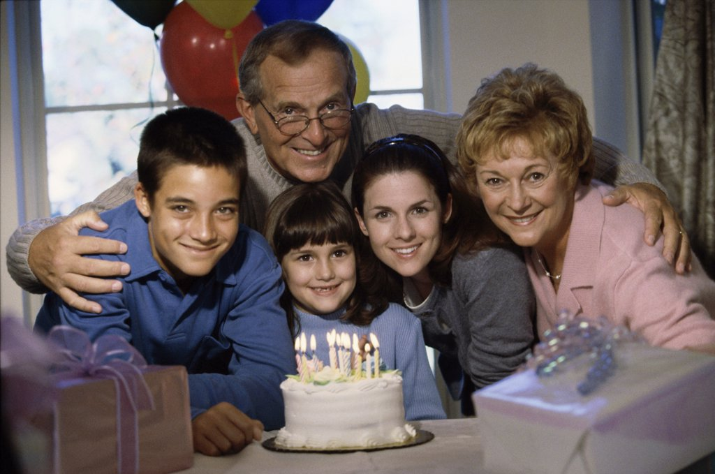 Portrait of grandparents and their grandchildren in front of a cake : Stock Photo