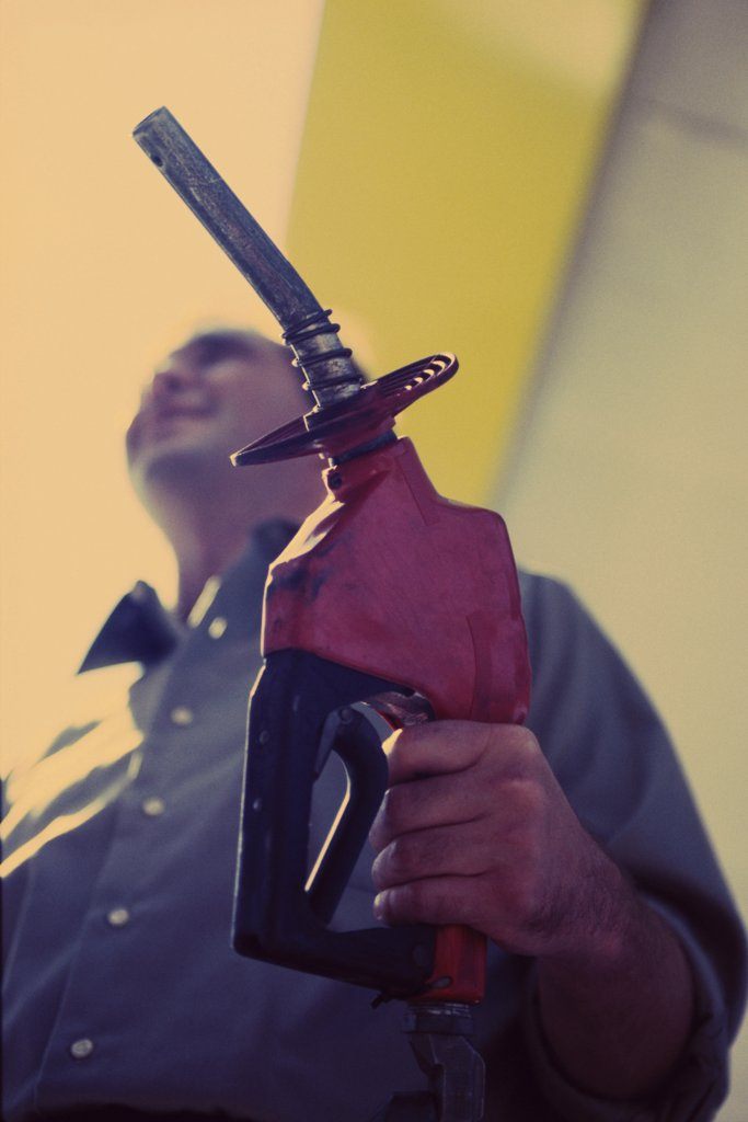 Low angle view of a gas station attendant holding a gas pump nozzle : Stock Photo