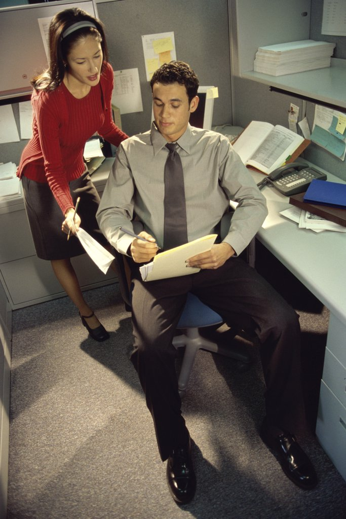 High angle view of a businessman and a businesswoman discussing a report : Stock Photo