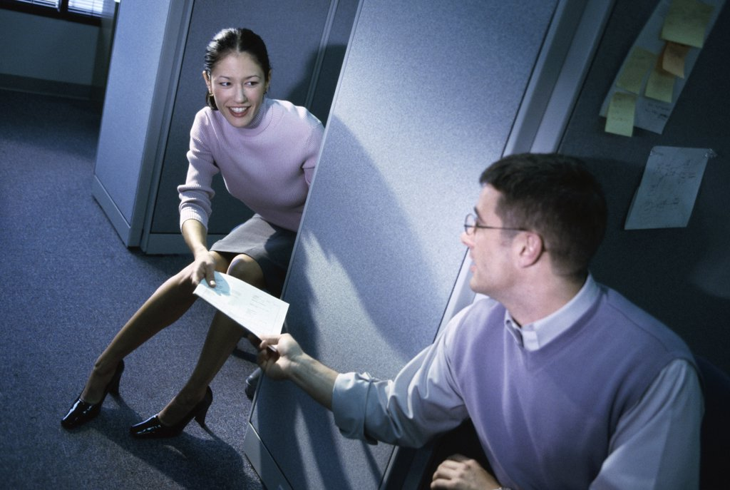 Businesswoman handing documents to a businessman in an office : Stock Photo