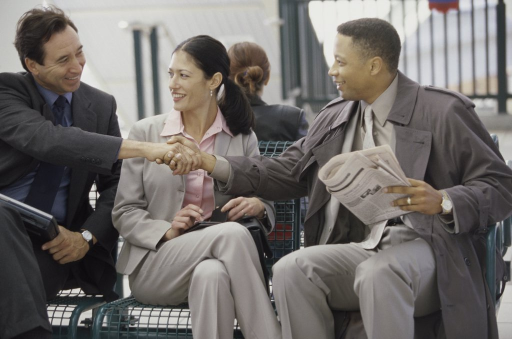 Stock Photo: 1574R-08104A Two businessmen and a businesswoman sitting together