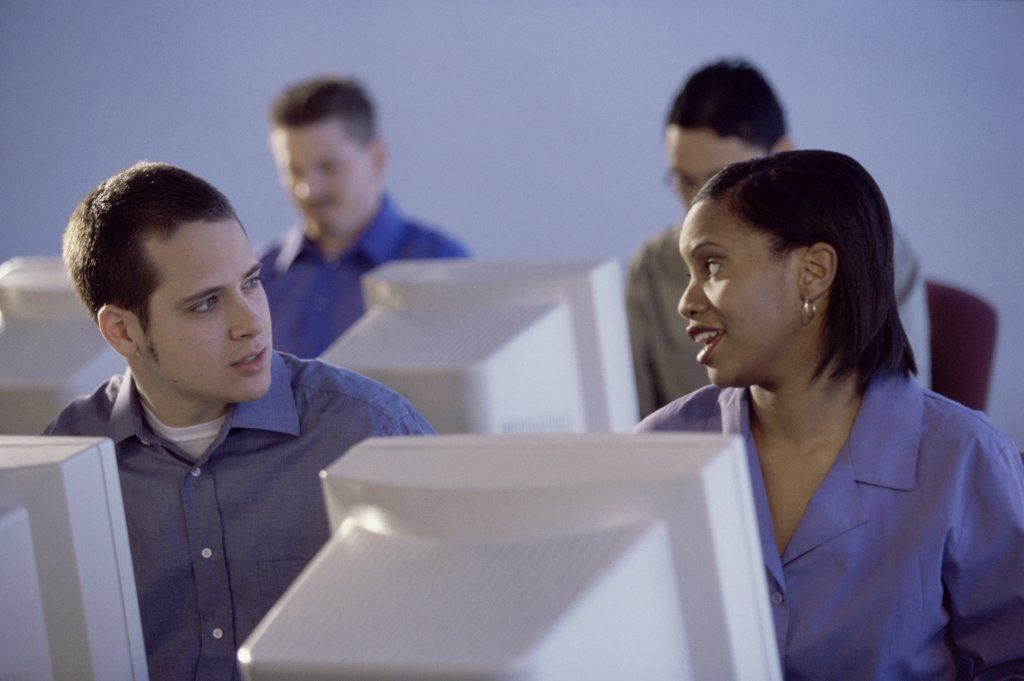 People sitting in front of computer monitors : Stock Photo