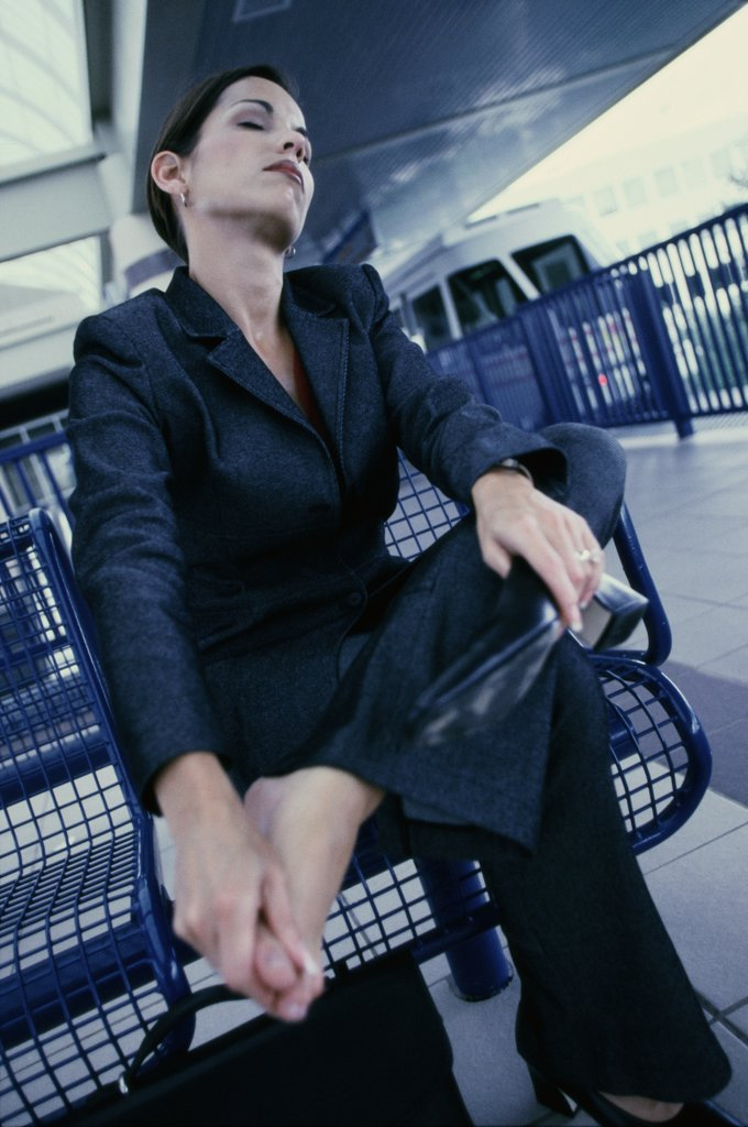 Low angle view of a young businesswoman sitting : Stock Photo
