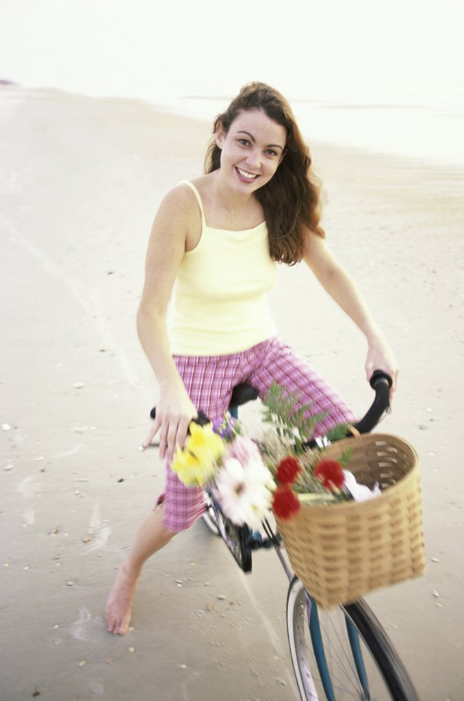 Portrait of a young woman sitting on a bicycle : Stock Photo