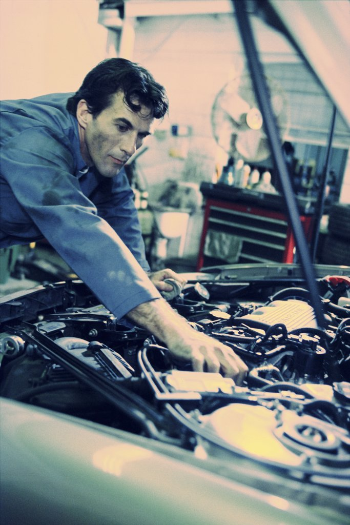 Auto mechanic working over the engine bay of a car : Stock Photo
