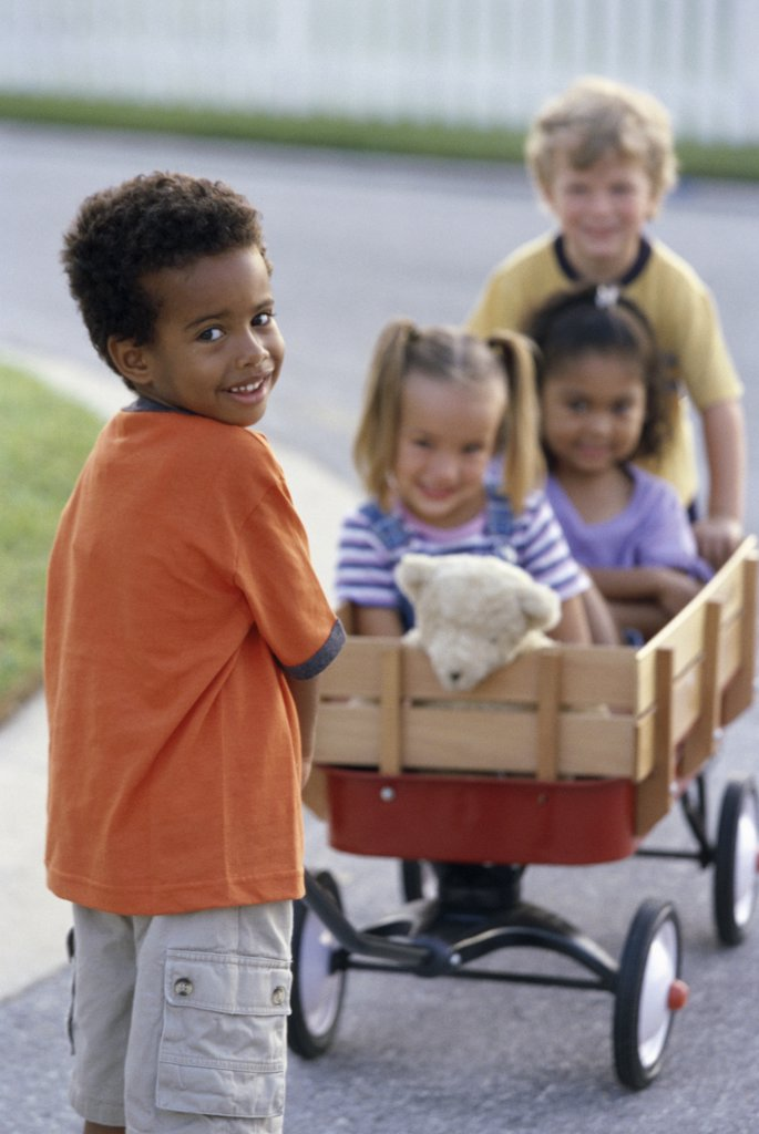 Portrait of two boys and two girls playing with a push cart : Stock Photo