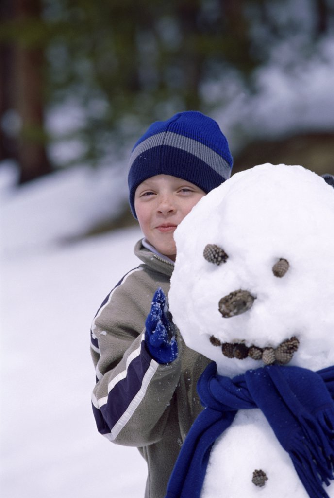 Portrait of a boy standing behind a snowman : Stock Photo