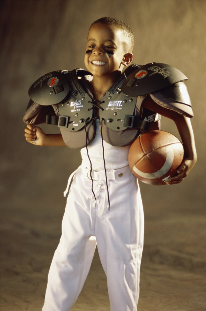 Stock Photo: 1574R-08467A Boy in a football uniform holding a ball