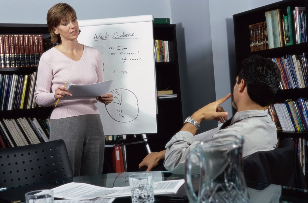 Stock Photo: 1574R-08486 Businesswoman and a businessman discussing in an office