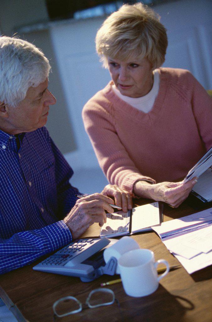 Senior couple writing a check : Stock Photo