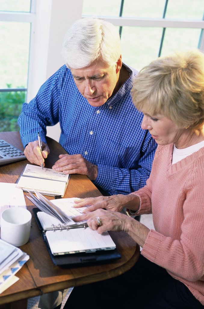 Senior couple sitting together calculating bills : Stock Photo