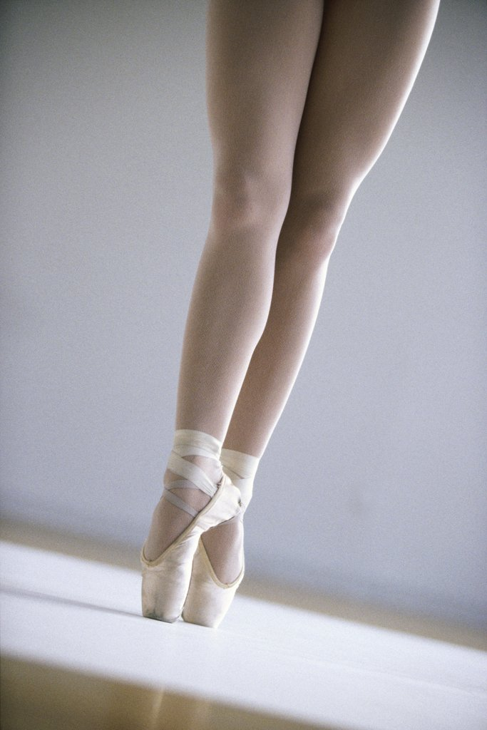 Low section view of a ballerina standing on tiptoe : Stock Photo