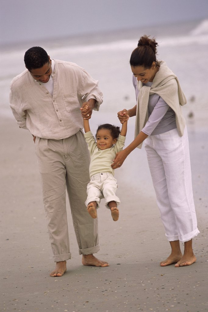 Father and mother walking with their daughter on the beach : Stock Photo