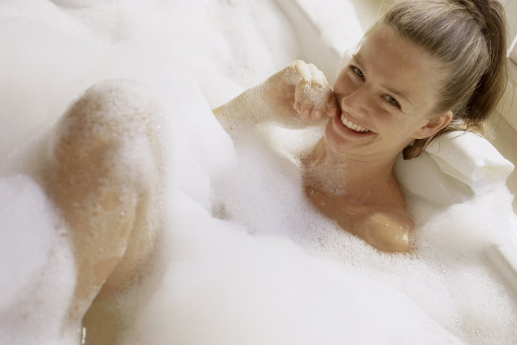 Portrait of a young woman in a bubble bath : Stock Photo
