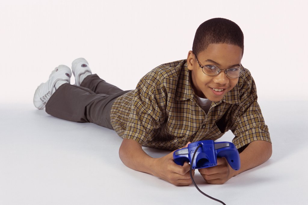 Portrait of a boy lying on the floor holding a game joystick : Stock Photo