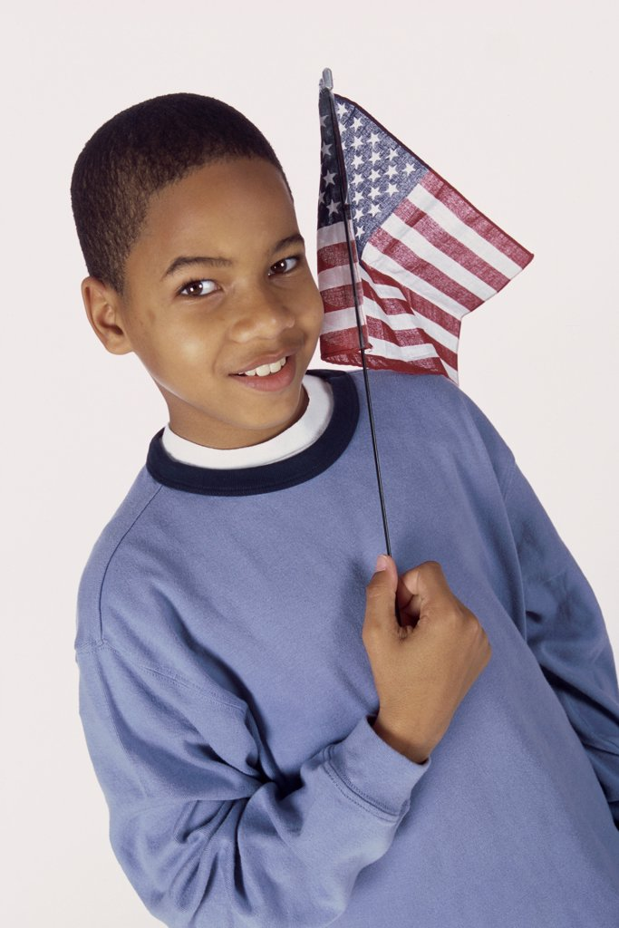 Portrait of a boy holding an American flag : Stock Photo