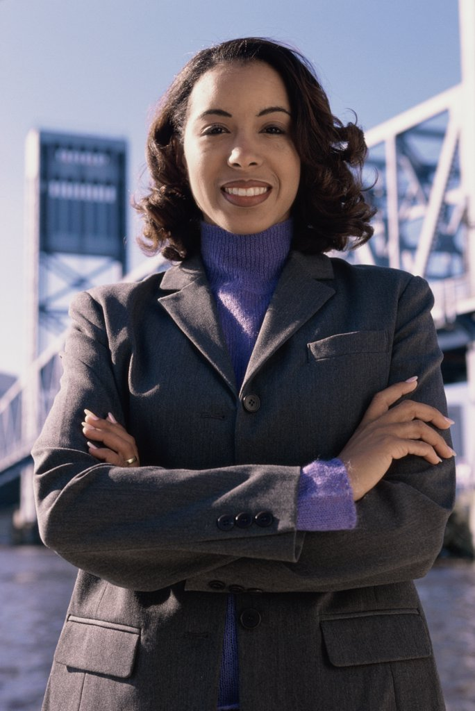 Portrait of a young businesswoman with her arms folded : Stock Photo
