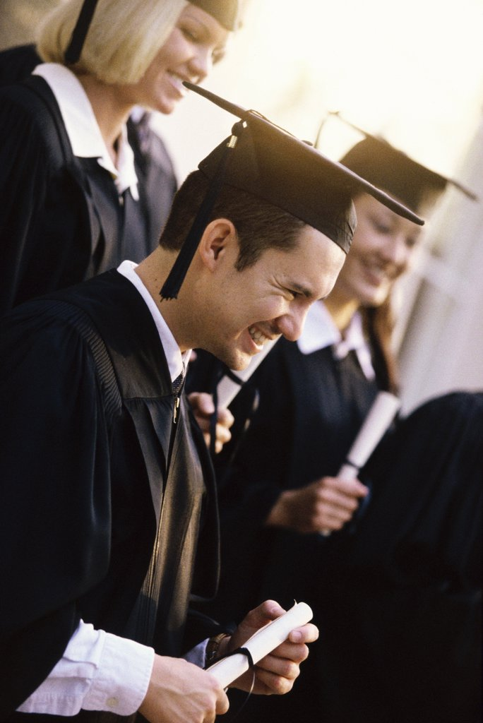 Side profile of young graduates holding diplomas smiling : Stock Photo