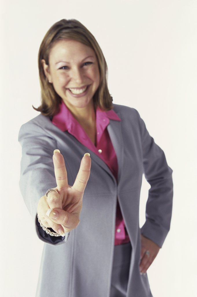 Stock Photo: 1574R-09009 Portrait of a businesswoman showing the victory sign