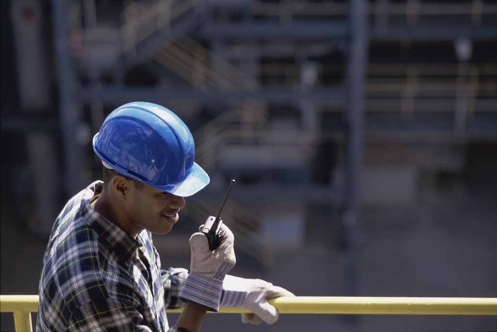 Construction worker talking on a walkie-talkie : Stock Photo