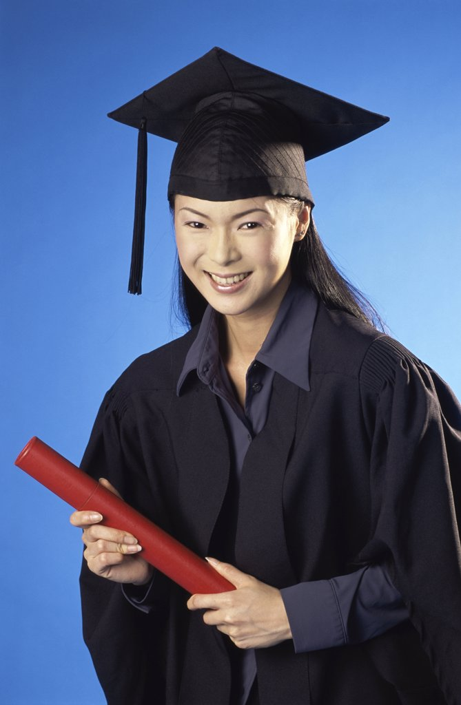 Young female graduate holding a diploma : Stock Photo
