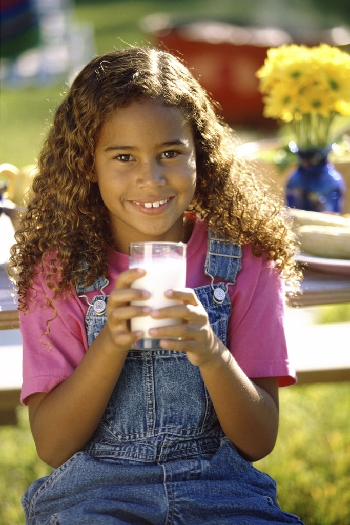Portrait of a girl holding a glass of milk : Stock Photo