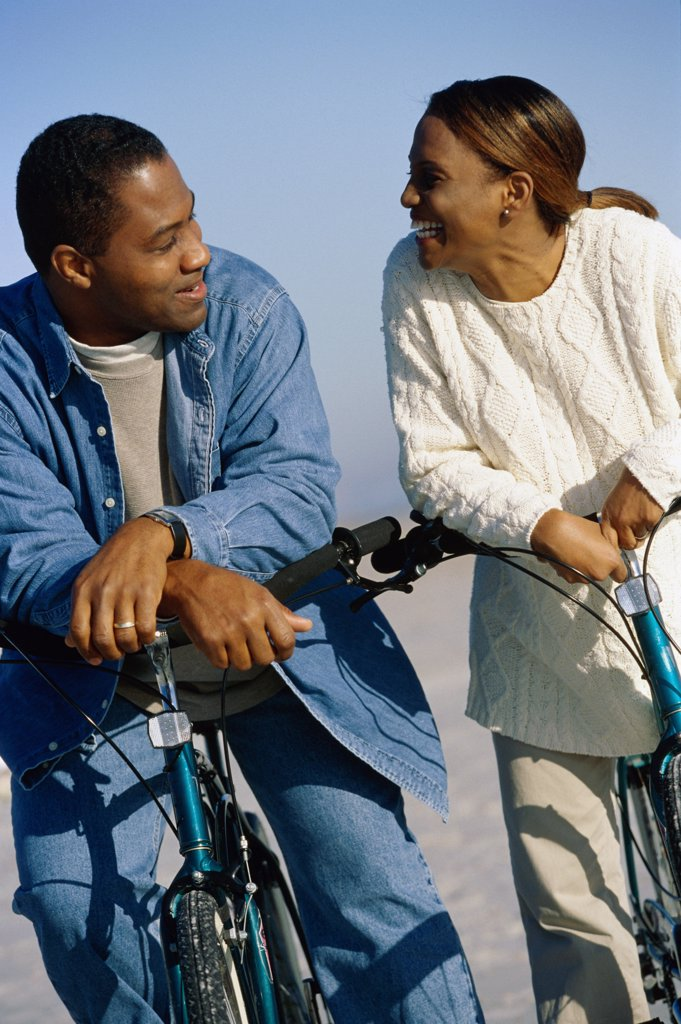 Stock Photo: 1574R-09240 Young couple on bicycles at the beach