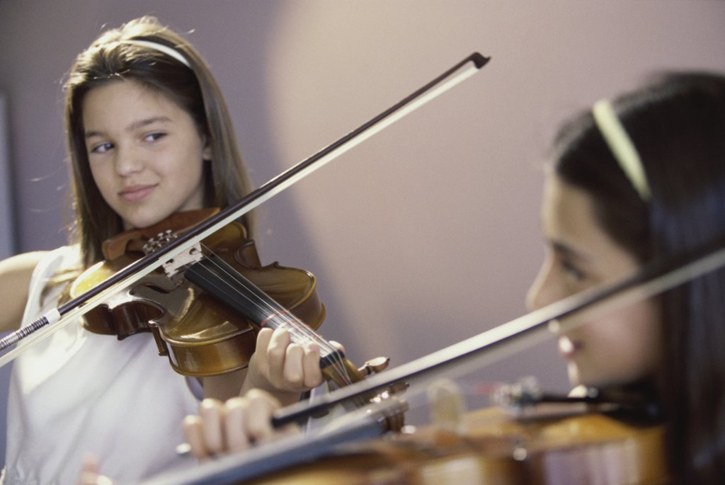 Two girls playing the violin : Stock Photo