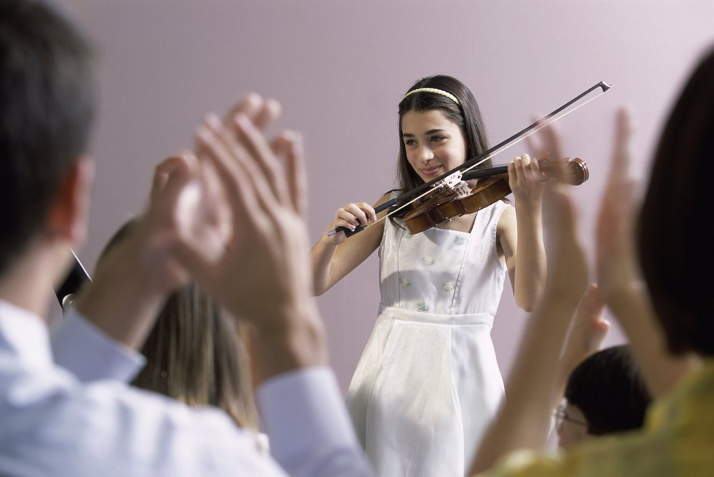 Girl playing a violin in front of an audience : Stock Photo
