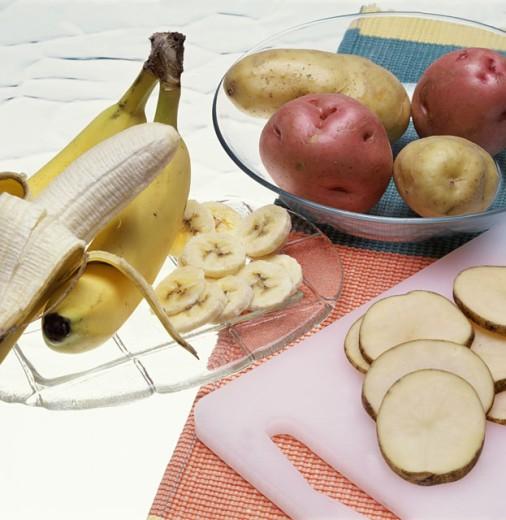 Close-up of bananas and potatoes : Stock Photo